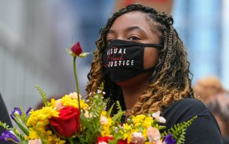 epa09224580 Protesters carry flowers as they march through the streets to commemorate the anniversary of George Floyd's death in Minneapolis, Minnesota, USA, 23 May 2021. The rally and march is part of several days of events to mark the one year anniversary of FloydÕs death that sparked the Black Lives Matter movement around the world.  EPA/CRAIG LASSIG