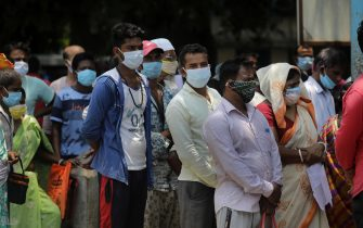 epa09206286 Fever patients wearing face protective masks wait without maintaining social distance for a test for COVID-19 at a test center during coronavirus pandemic crisis in Kalyani near Kolkata, eastern India, 17 May 2021.State Government imposed a new partial lockdown order to combat coronavirus pandemic in Kolkata. According to the Indian Ministry of Health, India recorded 311,000 fresh Covid-19 cases in the last 24 hours.  EPA/PIYAL ADHIKARY