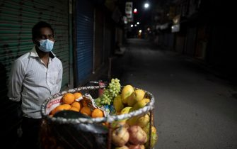 epa09217921 A fruit vendor waits for customers in an empty street during the COVID-19 lockdown in Kathmandu, Nepal, 21 May 2021. Nepal is struggling with record numbers of coronavirus disease (COVID-19) infections and deaths.  EPA/NARENDRA SHRESTHA