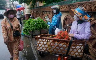 epa09224606 Vendors sell vegetables at a street in Phnom Penh, Cambodia, 24 May 2021. Authorities allowed all markets in Phnom Penh to re-open on 24 May 2021, a month after closing them to prevent the spread of the coronavirus disease (COVID-19) pandemic.  EPA/KITH SEREY