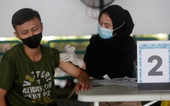 epa09224651 A doctor injects a dose of COVID-19 vaccine Astrazeneca during a mass vaccination for shop keepers at a shopping mall in Jakarta, Indonesia, 24 May 2021. The Indonesian government is accelerating the vaccination process due to an increasing number of Covid-19 cases after Eid AL-Fitr holydays.  EPA/ADI WEDA