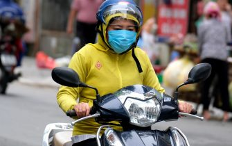 epa09162785 A woman wearing face mask rides motorbike at a street in Hanoi, Vietnam, 27 April 2021. Vietnamese Health Minister Nguyen Thanh Long has recently warned of a possible fourth COVID-19 wave, since the COVID-19 pandemic grows complicated in the neighboring countries of Cambodia and Laos.  EPA/LUONG THAI LINH