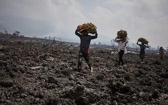Persone portano in salvo cibo e averi sulla lava a Kibati, in Congo, dopo l'eruzione del vulcano Nyiragongo