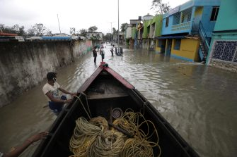 epa09228308 Villagers prepare a boat to rescue people amid a flood as Cyclone Yaas makes landfall in Digha, near the Bay of Bengal, south of Kolkata, India, 26 May 2021. The Odisha and Bengal governments started the evacuation of at-risk areas, as Cyclone Yaas hits the eastern coast of India.  EPA/PIYAL ADHIKARY