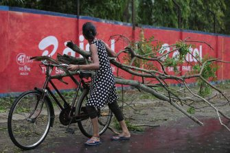 epa09228578 A woman carries fallen branches as Cyclone Yaas makes landfall in Digha, near the Bay of Bengal, south of Kolkata, India, 26 May 2021. The Odisha and Bengal governments started the evacuation of at-risk areas, as Cyclone Yaas hits the eastern coast of India.  EPA/PIYAL ADHIKARY