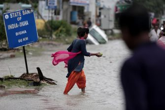epa09228571 Locals wade through a flooded area as Cyclone Yaas makes landfall in Digha, near the Bay of Bengal, south of Kolkata, India, 26 May 2021. The Odisha and Bengal governments started the evacuation of at-risk areas, as Cyclone Yaas hits the eastern coast of India.  EPA/PIYAL ADHIKARY