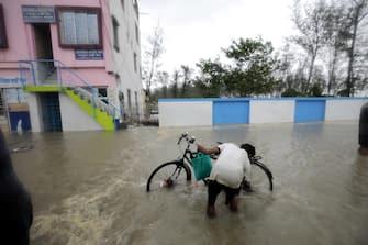 epa09228311 A commuter wades through flooded streets as Cyclone Yaas makes landfall in Digha, near the Bay of Bengal, south of Kolkata, India, 26 May 2021. The Odisha and Bengal governments started the evacuation of at-risk areas, as Cyclone Yaas hits the eastern coast of India.  EPA/PIYAL ADHIKARY