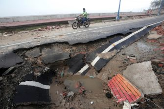 epa09230734 A man rides a bike on a damaged road after Cyclone Yaas hit Digha town near Bay of Bengal, Eastern India, 27 May 2021. The Odisha and the Bengal government ordered mass evacuations in the vulnerable areas after they issued an alert due to Cyclone Yaas.  EPA/PIYAL ADHIKARY