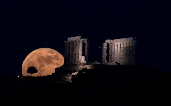 dpatop - 26 May 2021, Greece, Athen: The supermoon (flower Supermoon) rises behind the temple of Poseidon at Cape Sounion near Athens. Photo: Angelos Tzortzinis/dpa