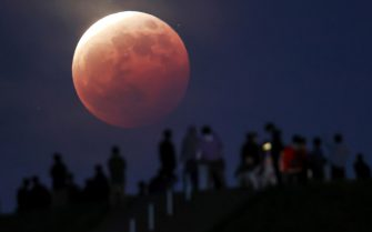 epa09230583 People watch the total eclipse of the moon at Moerenuma Park in Sapporo, northern Japan, 26 May 2021, as the super moon is passing through the shadow of the earth.  EPA/JIJI JAPAN OUT EDITORIAL USE ONLY/  NO ARCHIVES
