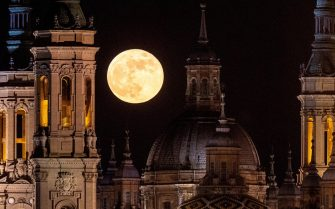 epa09230184 The full super moon rises above the El Pilar cathedral in Zaragoza, Spain, 26 May 2021.  EPA/Javier Belver