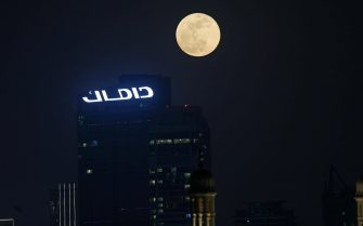 epa09229846 The Super Moon called the 'Flower Moon' rises in the sky of the Gulf emirate of Dubai, United Arab Emirates, 26 May 2021. The UAE will not be among the world's countries which are witnessing a blood super moon and total lunar eclipse like the US, Australia, South America and Eastern Asia.  EPA/ALI HAIDER