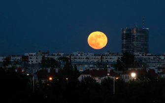 """The full moon, known as the """"Super Flower Moon"""" rises over the buildings in Zagreb, Croatia on May 26, 2021. Photo: Emica Elvedji/PIXSELL"""