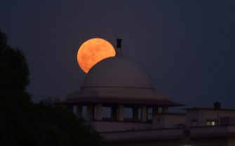 """NEW DELHI, INDIA - MAY 26: A full """"Super blood moon"""" seen from around india Gate on May 26, 2021 in New Delhi, India. The first total lunar eclipse in two years is set to take place on May 26 and it will be a Super blood moon. It will also be visible from some parts of the Pacific, the Atlantic, and the Indian ocean. This is a Super Blood Moon, where the moon appears reddish orange in colour and really big as well as it is a full moon and the satellite is closest to Earth. The eclipsed Moon is dimly illuminated by red-orange light left over from all of the sunsets and sunrises occurring around the world at that time. (Photo by Raj K Raj/Hindustan Times/Sipa USA)"""