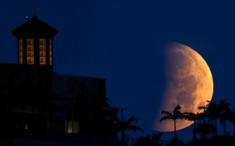 """The partially eclipsed moon sets over West Palm Beach Wednesday morning, May 26, 2021. The moon was near its closest approach to Earth, making it a """"supermoon,"""" and meaning it appears slightly larger in the sky. (Photo by Lannis Waters/Palmbeachpost/USA Today Network/Sipa USA)"""