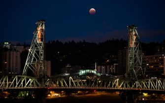 The eclipsed moon lies nestled between the trusses of the Hawthorne Bridge in Portland, Oregon in the early morning hours of May 26th, 2021. Wednesday's event was the first total lunar eclipse during a supermoon since September 28, 2015. (Mathieu Lewis-Rolland/Sipa USA)