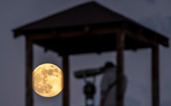 epaselect epa09227722 A man looks through binoculars at the full moon, the second and last super moon this year, called the 'Flower Moon,' as it rises over the castle in Skopje, Republic of North Macedonia, 25 May 2021.  EPA/GEORGI LICOVSKI
