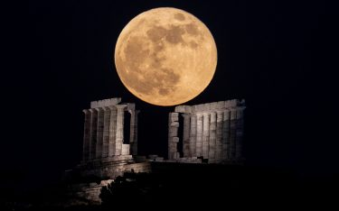 26 May 2021, Greece, Athen: The supermoon (flower Supermoon) rises behind the temple of Poseidon at Cape Sounion near Athens. Photo: Angelos Tzortzinis/dpa