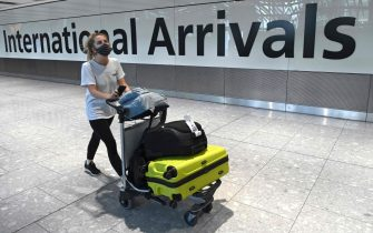 (FILES) In this file photo taken on July 10, 2020, a passenger wearing a face covering due to the COVID-19 pandemic, arrives at Heathrow airport, west London. - Britain will ban all arrivals from South American countries and Portugal from 0400 GMT Friday, January 15 over fears of importing a new coronavirus variant in Brazil, Transport Secretary Grant Shapps said Thursday. (Photo by DANIEL LEAL-OLIVAS / AFP)