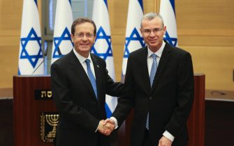 epa09242519 Presidential candidate Isaac Herzog (L) shakes hands with Yariv Levin, Speaker of the Knesset, during a special session of the Knesset whereby Israeli lawmakers elect a new president, at the plenum in the Knesset, Israel's parliament, in Jerusalem, 02 June 2021.  EPA/RONEN ZVULUN / POOL