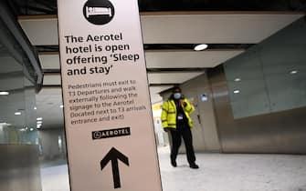 Addetta alla sicurezza cammina in un corridoio di un terminal di un aeroporto londinese