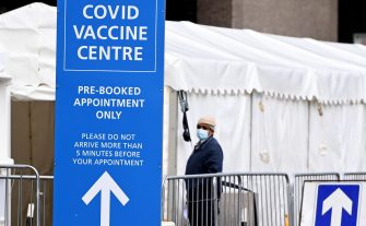 A man stands next to a Covid-19 vaccination centre in London, Britain, 10 February 2021. ANSA/ANDY RAIN
