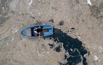 epa09247098 An aerial photo made with a drone shows a fisherman in a boat on the Marmara sea covered by sea snot in Istanbul, Turkey, 04 June 2021. Because of global heating, blanket of mucus-like substance in Marmara sea increasing day by day threatens fishing industry and the environment. Sea snot is formed as a result of the proliferation of microalgae called phytoplankton in the sea. The biggest reason for this is that the water temperature in the Marmara sea is 2.5 degrees above the average of the last 40 years.  EPA/ERDEM SAHIN