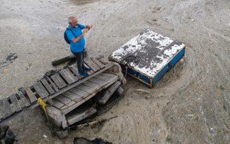 epa09247107 An aerial photo made with a drone shows a man takes picture of the Marmara sea covered by sea snot in Istanbul, Turkey, 04 June 2021. Because of global heating, blanket of mucus-like substance in Marmara sea increasing day by day threatens fishing industry and the environment. Sea snot is formed as a result of the proliferation of microalgae called phytoplankton in the sea. The biggest reason for this is that the water temperature in the Marmara sea is 2.5 degrees above the average of the last 40 years.  EPA/ERDEM SAHIN