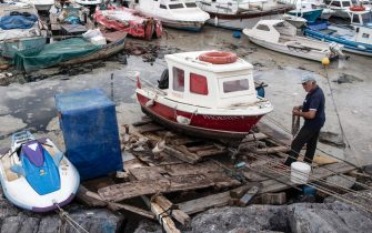 epa09247104 A fisherman works near a boat on the Marmara sea covered by sea snot in Istanbul, Turkey, 04 June 2021. Because of global heating, blanket of mucus-like substance in Marmara sea increasing day by day threatens fishing industry and the environment. Sea snot is formed as a result of the proliferation of microalgae called phytoplankton in the sea. The biggest reason for this is that the water temperature in the Marmara sea is 2.5 degrees above the average of the last 40 years.  EPA/ERDEM SAHIN