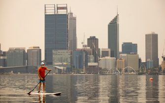 PERTH, AUSTRALIA - FEBRUARY 02:  A man paddles as smoke blankets the city skyline on February 2, 2021 in Perth, Australia. Up to 30 homes are feared lost as firefighters continue to work to bring the  Wooroloo bushfire under control in the Perth hills area. (Matt Jelonek/Getty Images)
