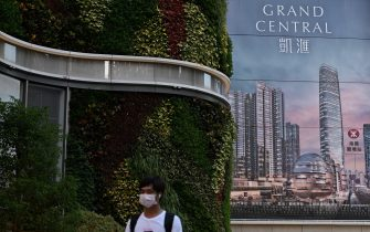 A man walks past a billboard for the Grand Central residential building complex in Hong Kong on May 28, 2021, where a 1.4 million USD (10.8 million HKD) one-bedroom apartment has been offered for a lucky draw's grand prize for which all Hong Kong residents aged 18 and above who have received both doses of the Covid-19 vaccines will be eligible to register. (Photo by Anthony WALLACE / AFP) (Photo by ANTHONY WALLACE/AFP via Getty Images)