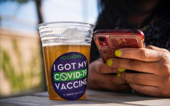 WASHINGTON, D.C. - MAY 06: Tamaria Kelly, 34, drinks a free beer after receiving a COVID-19 vaccine at the DC Health Department's Take the Shot, DC, walk-up clinic held at the John F. Kennedy Center for the Performing Arts' outdoor Victura Park at the REACH on Thursday, May 06, 2021 in Washington, D.C. Attendants were provided with a single dose of the Johnson & Johnson vaccine and offered a free beer, courtesy of Solace Brewing Co., as part of D.C.s Vaxed for Mom initiative. (Photo by Amanda Voisard/for The Washington Post via Getty Images)