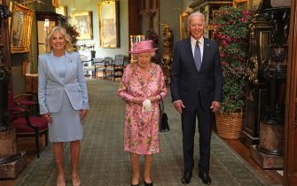 TOPSHOT - US President Joe Biden (R) and US First Lady Jill Biden (L) pose for a photograph with Britain's Queen Elizabeth II  (C) in the Grand Corridor at Windsor Castle in Windsor, west of London, on June 13, 2021, before taking tea. - US president Biden will visit the queen at Windsor Castle late Sunday, where he and First Lady Jill Biden will take tea with the queen. (Photo by Steve Parsons / POOL / AFP) (Photo by STEVE PARSONS/POOL/AFP via Getty Images)