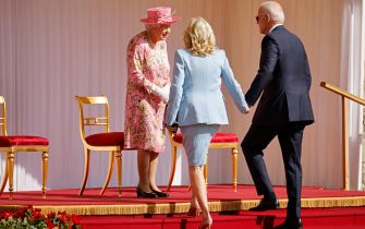 Britain's Queen Elizabeth II (L) greets US President Joe Biden (R) and US First Lady Jill Biden (C) at the dais in the Quadrangle of Windsor Castle in Windsor, west of London, on June 13, 2021. - US president Biden will visit Windsor Castle late Sunday, where he and First Lady Jill Biden will take tea with the queen. (Photo by Tolga Akmen / AFP) (Photo by TOLGA AKMEN/AFP via Getty Images)