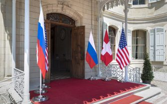 epa09273037 Flags of the US, Russia and Switzerland photographed in front of the entrance of the villa La Grange, one day prior to the US - Russia summit in Geneva, Switzerland, 15 June 2021. The meeting between US President Joe Biden and Russian President Vladimir Putin is scheduled in Geneva for 16 June 2021.  EPA/PETER KLAUNZER