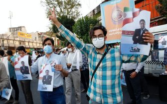 epa09273440 Supporters of Iranian presidential candidate Abdolnaser Hemati hold pictures of him, during an election campaign rally in Tehran, Iran, 15 June 2021. Iranians will vote in a presidential election on 18 June 2021.  EPA/ABEDIN TAHERKENAREH