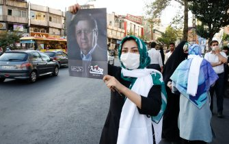 epa09273443 Supporters of Iranian presidential candidate Abdolnaser Hemati hold pictures of him, during an election campaign rally in Tehran, Iran, 15 June 2021. Iranians will vote in a presidential election on 18 June 2021.  EPA/ABEDIN TAHERKENAREH