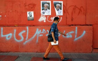 epa09274028 An Iranian man walks next to the posters of Iranian presidential candidate Saeed Jalili and a hand writing reads in Persian 'We will vote' in a street in Tehran, Iran, 15 June 2021. Iranians will vote in a presidential election on 18 June 2021.  EPA/ABEDIN TAHERKENAREH