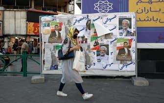epa09274023 An Iranian woman walks past elections billboard in a street in Tehran, Iran, 15 June 2021. Iranians will vote in a presidential election on 18 June 2021.  EPA/ABEDIN TAHERKENAREH