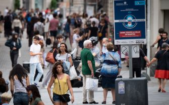 Pedestrians walk down a street near a remaining sign indicating to wear face masks in downtown Nantes, on June 17, 2021, as people are allowed in France to remove face masks when outside for the first time since autumn 2020. - The easing of coronavirus rules came as authorities hailed a rapid decline in new cases on the eve of summer holidays. The nationwide curfew of 11 pm will also be lifted ahead of schedule on June 20, 2021. (Photo by LOIC VENANCE / AFP) (Photo by LOIC VENANCE/AFP via Getty Images)