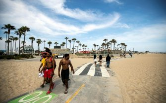 epa09275093 People walk along the beach without wearing face masks as California drops most of its restrictions put in place in response to the COVID-19 pandemic, in Venice Beach, California, USA, 15 June 2021.  EPA/ETIENNE LAURENT