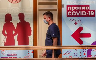 epa09282548 A man wearing a face mask passes the vaccination point at the State Department Store GUM in Moscow, Russia, 18 June 2021. Over the past 24 hours, 9,056 cases of COVID-19 coronavirus infection have been detected in Moscow, which has become a new absolute record since the beginning of the pandemic.  Mass entertainment events with more than 1,000 participants are prohibited in Moscow, while dance floors and fan zones for football fans are being closed.  EPA/SERGEI ILNITSKY