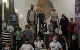 epa09282545 People wearing face masks walk in front of a portrait of Soviet Union founder Vladimir Lenin at the Metro station Biblioteka Lenina in Moscow, Russia, 18 June 2021. Over the past 24 hours, 9,056 cases of COVID-19 coronavirus infection have been detected in Moscow, which has become a new absolute record since the beginning of the pandemic. Mass entertainment events with more than 1,000 participants are prohibited in Moscow, while dance floors and fan zones for football fans are being closed.  EPA/SERGEI ILNITSKY