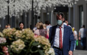 epa09283054 A man wearing a face mask walks in downtown Moscow, Russia, 18 June 2021. Over the past 24 hours, 9,056 cases of COVID-19 coronavirus infection have been detected in Moscow, which has become a new absolute record since the beginning of the pandemic.  Mass entertainment events with more than 1,000 participants are prohibited in Moscow, while dance floors and fan zones for football fans are being closed.  EPA/SERGEI ILNITSKY