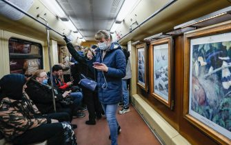 epa09112008 People wear protective face masks in a metro carriage decorated with reproductions of paintings by famous artists in Moscow, Russia, 02 April 2021, amid the COVID-19 coronavirus pandemic.  EPA/YURI KOCHETKOV
