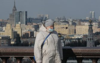 epa09117147 A woman wearing a protective face mask walks on the street in Moscow, Russia, 05 April 2021, amid the COVID-19 coronavirus pandemic.  EPA/SERGEI ILNITSKY