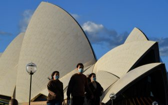epa09302260 Pedestrians wearing face masks walk past the Sydney Opera House in Sydney, New South Wales (NSW), Australia, 26 June 2021. All of greater Sydney, the Central Coast, the Blue Mountains and Wollongong regions will enter a two-week coronavirus lockdown until 09 July and new restrictions will be in place for the remainder of New South Wales.  EPA/MICK TSIKAS AUSTRALIA AND NEW ZEALAND OUT