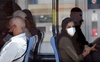 Israelis wear protective masks against Covid-19 inside a light train in Jerusalem on June 25, 2021. - The Israeli health ministry reimposed a requirement for masks to be worn in enclosed public places following a surge in Covid cases since it was dropped 10 days ago. (Photo by Emmanuel DUNAND / AFP) (Photo by EMMANUEL DUNAND/AFP via Getty Images)