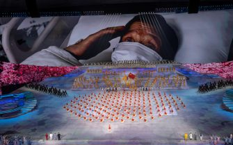 BEIJING, CHINA - JUNE 28: A patient wears a mask as he is seen on a large screen as dancers take part in a scene about the COVID-19 pandemic  at a mass gala marking the 100th anniversary of the Communist Party on June 28, 2021 at the Olympic Bird's Nest stadium in Beijing, China. China will officially mark the 100th anniversary of the founding of the Communist Party on July 1st. (Photo by Kevin Frayer/Getty Images)