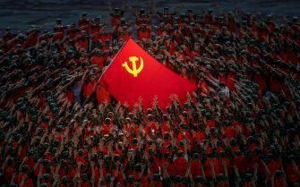 BEIJING, CHINA - JUNE 28: Performers in the costume of emergency workers surround a large Communist Party flag during a mass gala marking the 100th anniversary of the Communist Party on June 28, 2021 at the Olympic Bird's Nest stadium in Beijing, China. China will officially mark the100th anniversary of the founding of the Communist Party on July 1st. (Photo by Kevin Frayer/Getty Images)